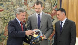 Carlos Sainz entrega un casco al rey