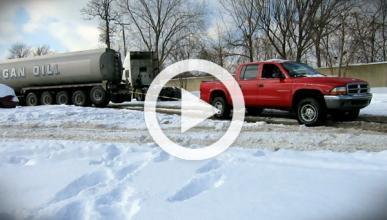 Una pick-up remolca a un camión en la nieve