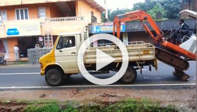 Un indio sube una excavadora a un remolque a golpe de pala