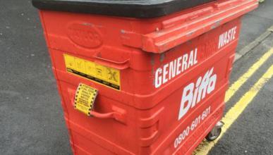 Un policía multa un contenedor de basura mal estacionado