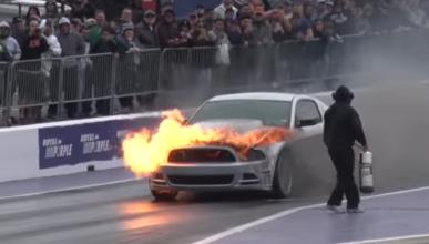 Un Ford Mustang envuelto en llamas en una drag race