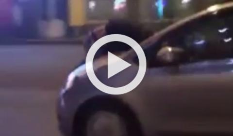 Una mujer conduce un coche con su marido sobre el capó