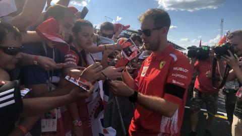 Vettel firma autógrafos