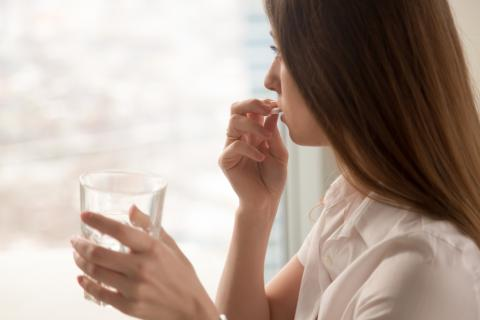 Mujer tomando una pastilla