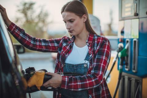 Una mujer echando gasolina a su coche