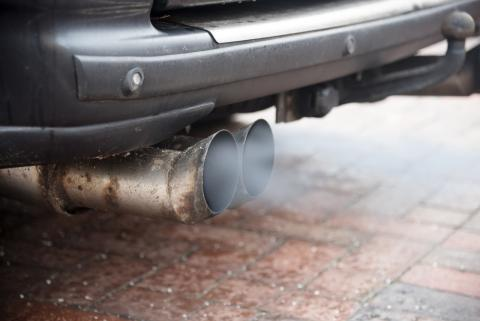 El humo del motor sale por el tubo de escape de un coche