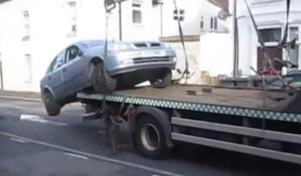 Baja el coche de la grúa marcha atrás de un salto