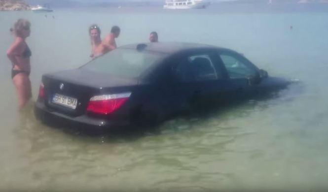 Aparca su BMW Serie 5 en una playa con bañistas
